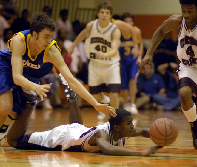 Henderson County's Josh Terry shuffles the ball to Darius Haygan (4) who takes it in for the layup as Caldwell County's Matt Fraliex (5) closes in during the 2007 Second Region Tournament game in Hopkinsville.