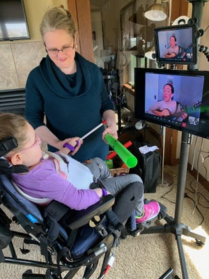 Rachael Willeke sings to Payton Williams on-screen during a virtual music therapy session as mother Brenda Buikema assists in their North Liberty home.