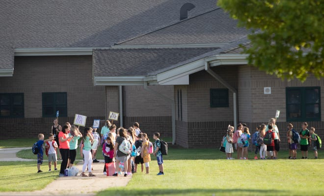 Students line up to enter Natalie Kreeger Elementary school in Fowlerville Monday, Aug. 30, 2021.