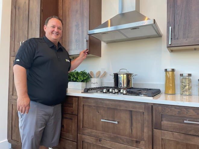 Matt Norton, sales director for Cabinets Express, demonstrates the features of a hickory kitchen cabinet line at the Brighton-based company's new store off Grand River Avenue in Brighton Township, Wednesday, Aug. 25, 2021.