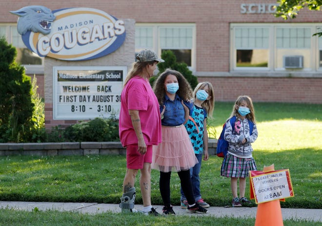 Masked students wait outside of Madison Elementary School on the first day of classes, Monday, August 30, 2021, in Manitowoc, Wis. The Manitowoc school system is requiring masks to fight COVID infections.