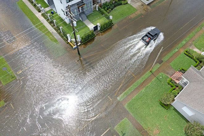 A truck drives through flooded streets in the Lakeview neighborhood of New Orleans in the aftermath of Hurricane Ida on Monday, August 30, 2021.