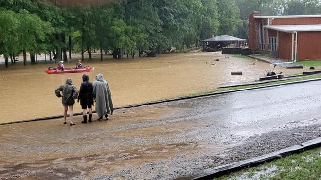 Members of the Tennessee City Volunteer Fire Department rescue people from the Camp Garner Creek grounds during the Aug. 21 floods.