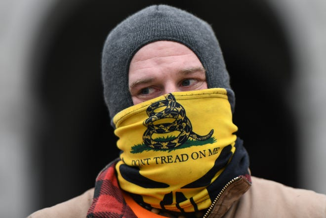 """A supporter of President Donald Trump wearing a """"Don't Tread on Me"""" face mask demonstrates outside the Pennsylvania Capitol Building on Jan. 17, 2021, in Harrisburg, Pennsylvania. (Mark Makela/Getty Images/TNS)"""