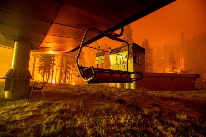 Seen in a long camera exposure, the Caldor Fire burns at Sierra-at-Tahoe ski resort on Aug. 30, 2021, in Eldorado National Forest, Calif. The main buildings at the ski slope's base survived as the main fire front passed.