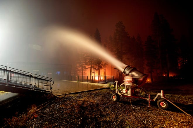 Seen in a long camera exposure, a snowmaking machine blasts water as the Caldor Fire burns at Sierra-at-Tahoe ski resort on Monday, Aug. 30, 2021, in Eldorado National Forest, Calif. The main buildings at the ski slope's base survived as the main fire front passed. (AP Photo/Noah Berger)