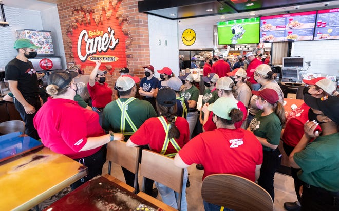 Adrianna Casillas, left, leads crew members, also known as Fry Cook & Cashier, in training Monday, August 30, 2021 before they serve family and community members during a soft opening at Raising Cane's Chicken Fingers in Visalia. The grand opening is Tuesday.