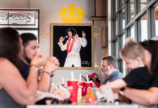 The Elvis Presley picture is one of several decorations common to all restaurants in the Raising Cane's Chicken Fingers chain. Crew members served family and community members during Monday's soft opening in Visalia. The grand opening is Tuesday.