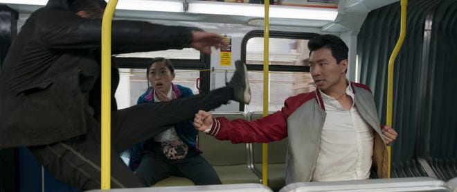 """Shang-Chi (Simu Liu) roughs up a bad guy as best friend Katy (Awkwafina) looks on in """"Shang-Chi and the Legend of the Ten Rings."""""""