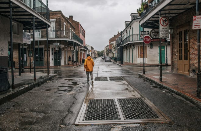 A person walks through New Orleans' French Quarter ahead of Hurricane Ida. Residents of New Orleans prepare as the outer bands of the hurricane begin to cut across the city.