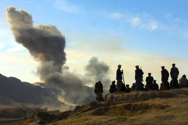 In this Nov. 19, 2001 photo, Northern Alliance soldiers watch as U.S. air strikes pound Taliban positions in Kunduz province near the town of Khanabad, Afghanistan. [ASSOCIATED PRESS/IVAN SEKRETAREV/FILE]