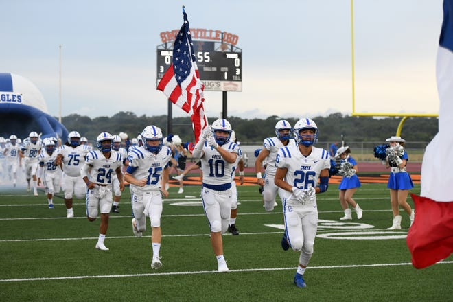 Cedar Creek players run onto the field before a 42-0 loss to Smithville in both teams' season opener.