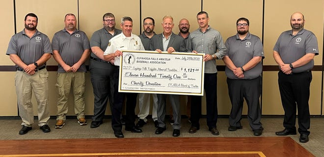 The Cuyahoga Falls Amateur Baseball Association recently donated $1,121 to the Cuyahoga Falls Firefighter Memorial Foundation to help pay for the creation of a new memorial to honor the city's firefighters. This check presentation occurred at the Cuyahoga Falls City Council meeting on July 26. Pictured in the front row from left are:  Fire Chief Chris Martin, Mayor Don Walters, and Fire Capt. Matt Kee. In the back row from left are: CFABA H League President Greg Nowak, CFABA Board member Larry Forinash, Board Secretary Ryan Kinnan, Board President Andrew Cole, Board Treasurer Mike DeSessa, Director of Fundraising Steve DeArdo and Chief Umpire Tony Bianchi.