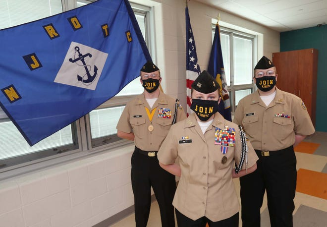 Navy Junior Reserve Officers Training Corps  cadets Seth Young, 16, left, and Nick Hartley, 16, right, stand with the unit commander, Amelia Pritt, 17, at Ellet High School in Akron.