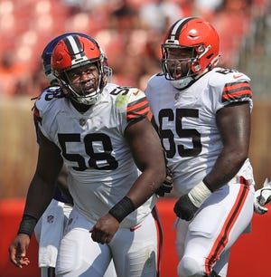 Browns defensive tackle Malik McDowell (58) is congratulated by defensive tackle Marvin Wilson (65) after a sack during the second half of a preseason win over the New York Giants in Cleveland. [Jeff Lange/Beacon Journal]