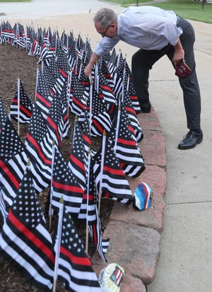 Stow Mayor John Pribonic picks up a stone placed between flags in honor of firefighters killed on September 11 in the 9/11 Memorial Garden in front of Stow Town Hall.  Residents can paint stones to commemorate September 11 and add them to the garden.  There are also flags honoring fallen police and paramedics.