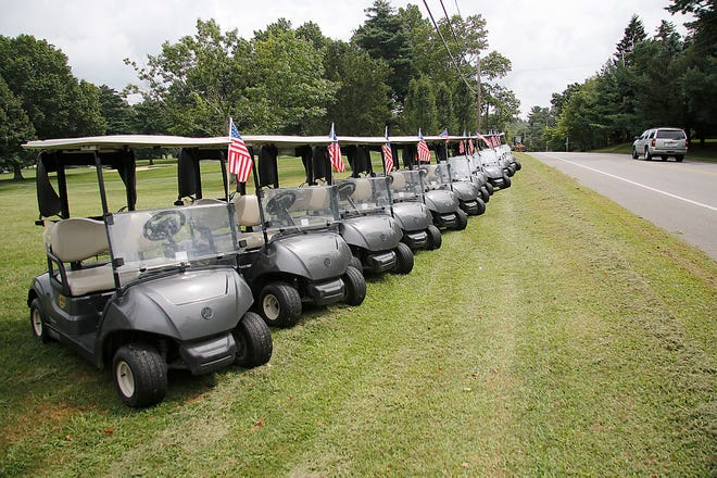 Golf carts are lined up with American flags on them along Center Street on Monday at the Ashland Golf Club in memory of the 13 U.S. service members killed in the Kabul airport attack in Afghanistan.