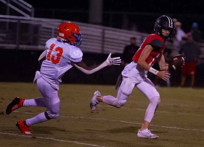 Augusta Christian QB Jeb Bradford scrambles past Ronald Smith of Johnson High School and scores on a 31 yard run at the high school football game between Augusta Christian and Johnson High School on August 19, 2021 in North Augusta, SC. [MIKE ADAMS FOR THE AUGUSTA CHRONICLE]