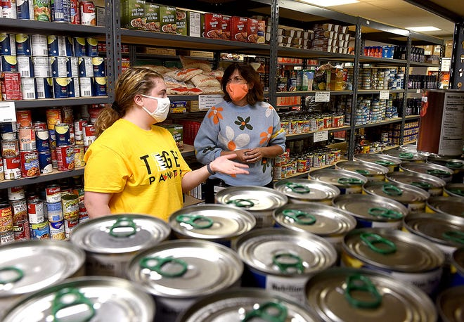 Chelsie Mackanos, left, a sophomore at the University of Missouri and ambassador for the Tiger Pantry, talks to Angela Tennison, assistant dean of the University of Missouri College of Veterinary Medicine, on Tuesday during an open house of the new location of the Tiger Pantry, Truman's Closet and Stripes on the lower floor of the Hitt Street Garage at 301 Hitt St.