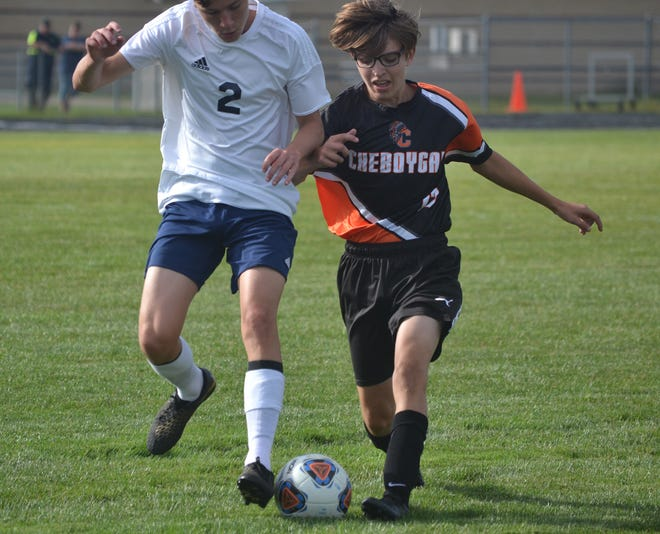 Cheboygan sophomore Kelsey Lamb, right, and Big Rapids Crossroads' Trystan Buhmann (2) battle for the ball during the first half of a varsity boys soccer matchup in Cheboygan on Monday.