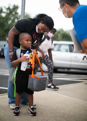 Jeremiah Richardson, 5, with his mother, Frantasia, as he gets ready to go into Southwood Elementary School Tuesday on the first full day of kindergarten for Columbus City Schools.