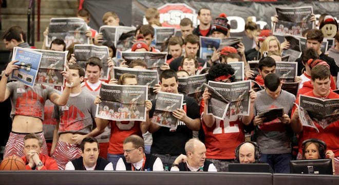 Ohio State University students sitting in the Buckeye Nuthouse section hold up copies of today's Columbus Dispatch as Michigan players are introduced during Tuesday's NCAA Division I basketball game at Value City Arena in Columbus on Tuesday, Jan. 13, 2015. (Dispatch Photo by Barbara J. Perenic)