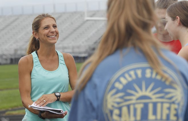 """First-year Central Crossing cross country coach Laura Kaulen talks to her runners before practice Aug. 30. Kaulen, who runs marathons and has participated in the Olympic Trials, said she is excited to """"share my passion with young athletes."""""""