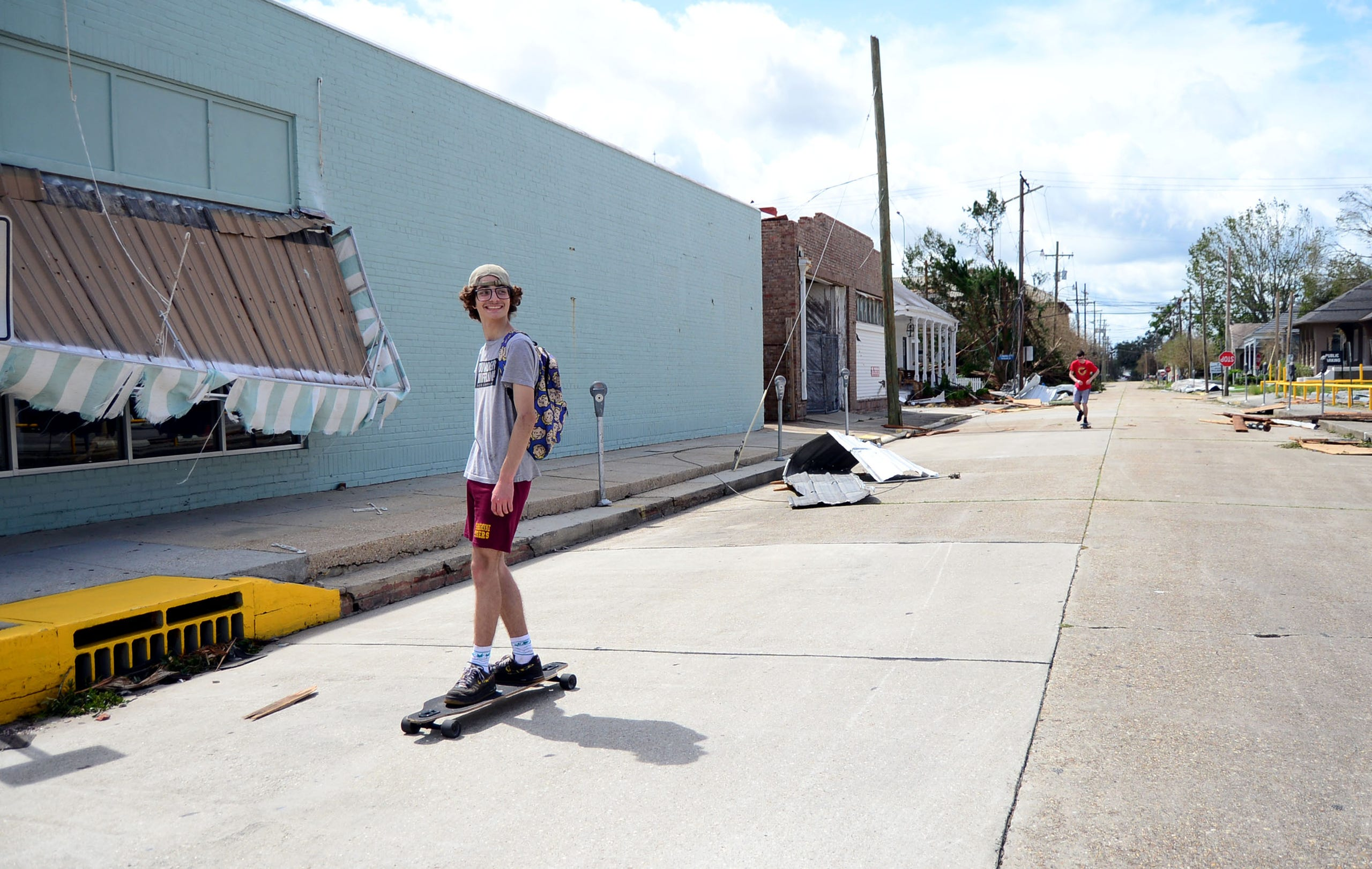 Two people skateboard in near downtown Houma on Monday, Aug. 30, 2021. Storm damage and debris can be seen along the street.