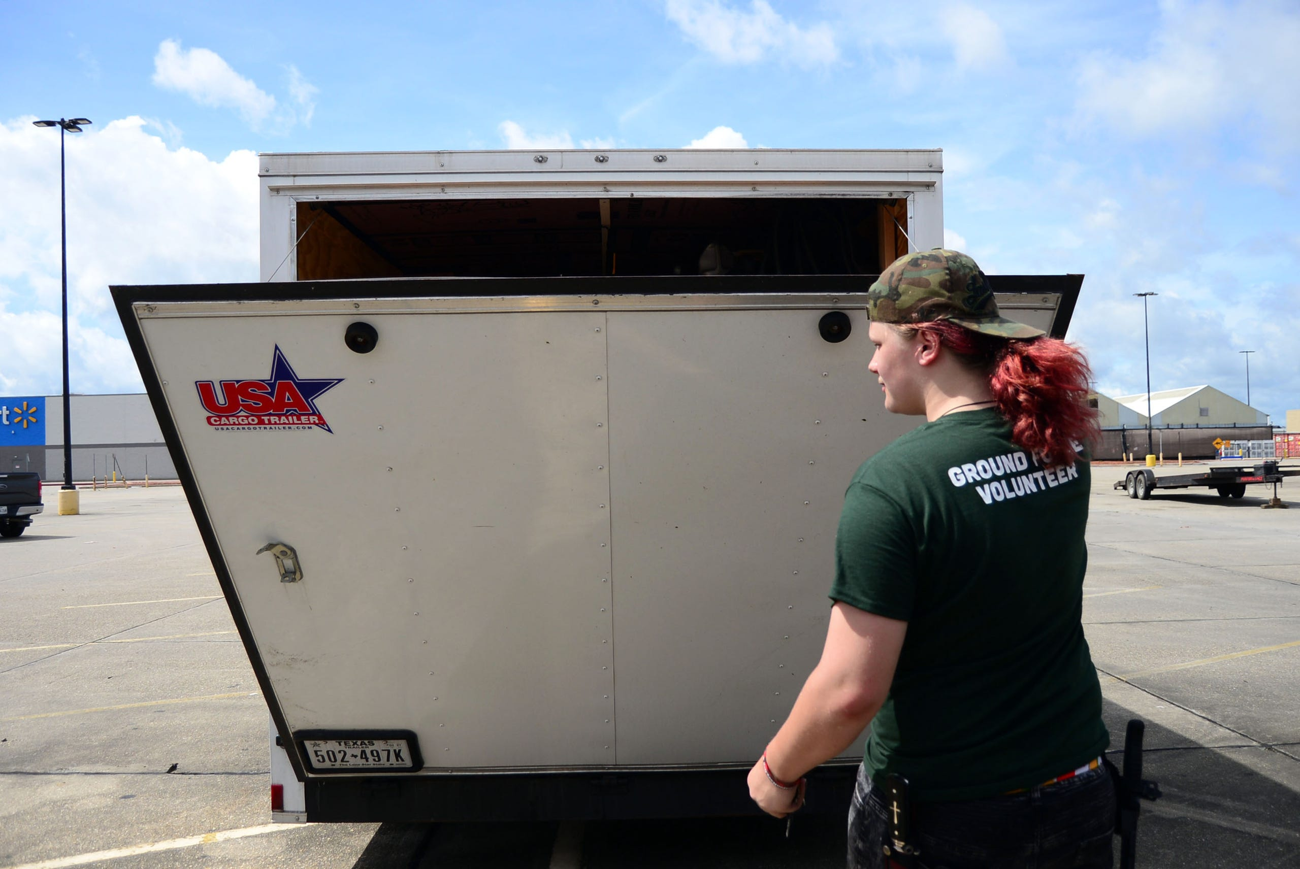A teenage volunteer with the Cajun Navy Foundation's Ground Force opens the back of a Cajun Navy trailer containing supplies to distribute to residents in Houma.