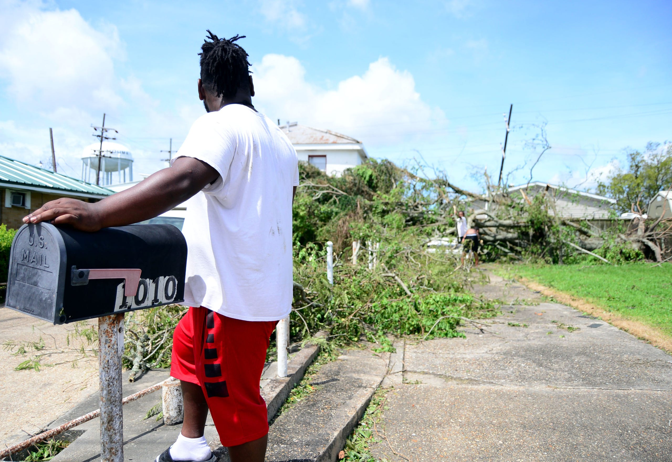 Paten Neville stands next to the mailbox outside his mother's home in Houma, La., on Monday, Aug. 30, 2021. His car, barely seen in the background, is buried underneath a tree that fell from Hurricane Ida's winds on Sunday.