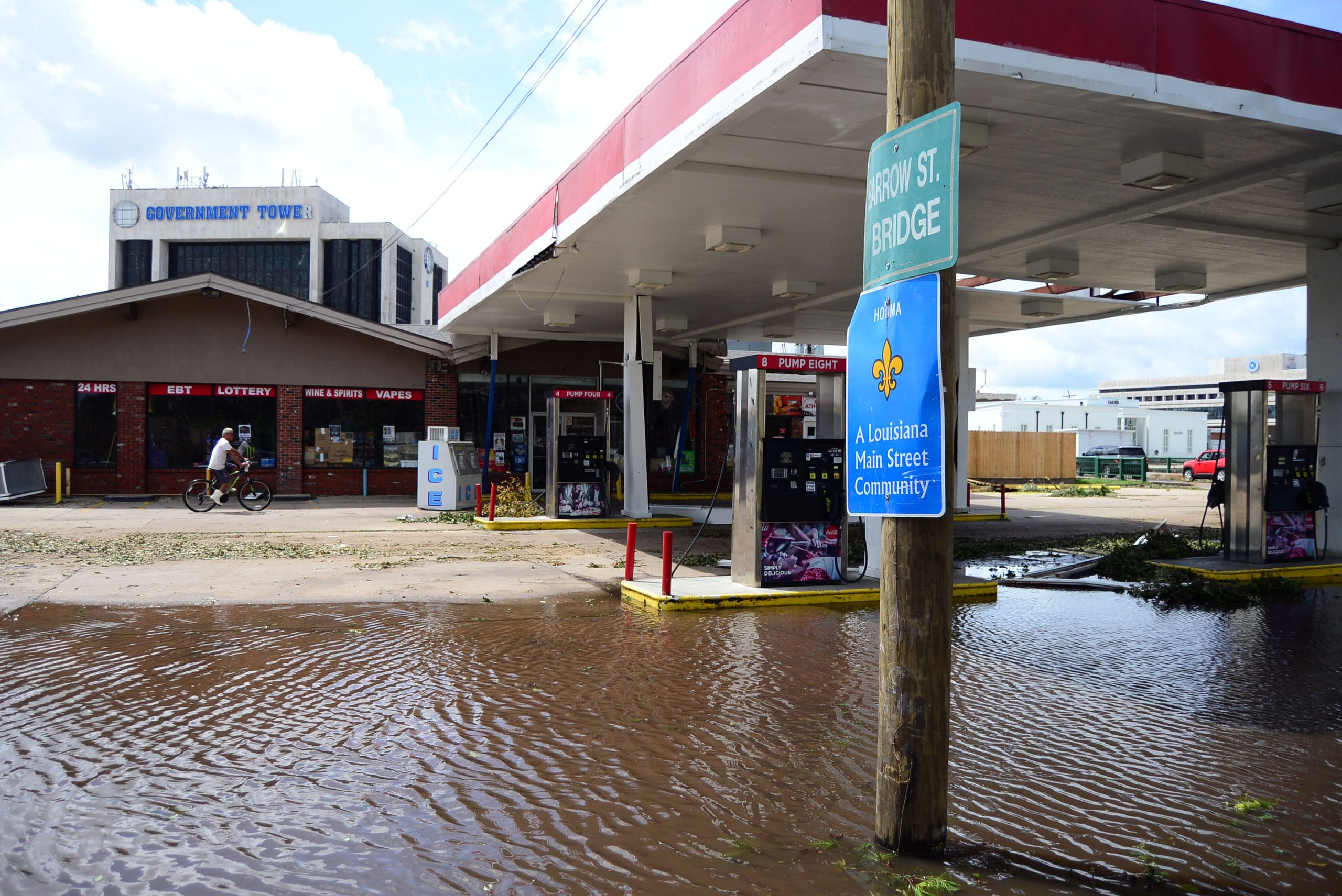 A person is seen riding a bike on Monday, Aug. 30, 2021, past a gas station that has mild flooding in its parking lot in Houma, La.