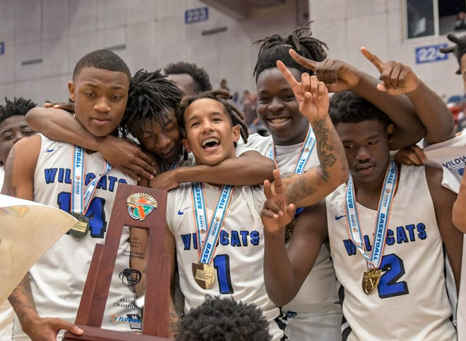 The Wildwood boys basketball teams celebrate after winning the 2021 Class 1A state championship at the RP Funding Center in Lakeland. The team's success played a big role in helping the Wildcats earn the Floyd E. Lay Sunshine Cup All-Sports by the FHSAA as the boys for field the top Class 1A school for the overall success of its boys sports programs.. [PAUL RYAN / CORRESPONDENT]