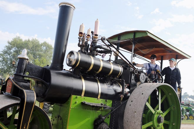 Russell Heerdt of Durango, Colorado, gives his girlfriend, Kylah Thompson, some pointers on operating a 1905 12 ton Kelly-Springfield Road Roller Aug. 30, 2018, during the Midwest Old Threshers Reunion at Mount Pleasant's McMillan Park. The five-day festival kicks off with a parade Wednesday and continues through Labor Day.