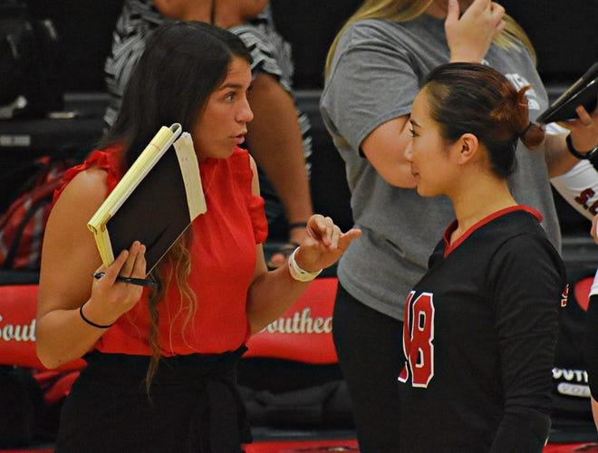 Southeastern Community College interim head volleyball coach Danielle Coronado (left) confers with libero Ayaka Yoshioka during a timeout Monday against William Penn University's junior varsity at Loren Walker Arena. The Statesmen won the first match and SCC swept Penn in the second one.