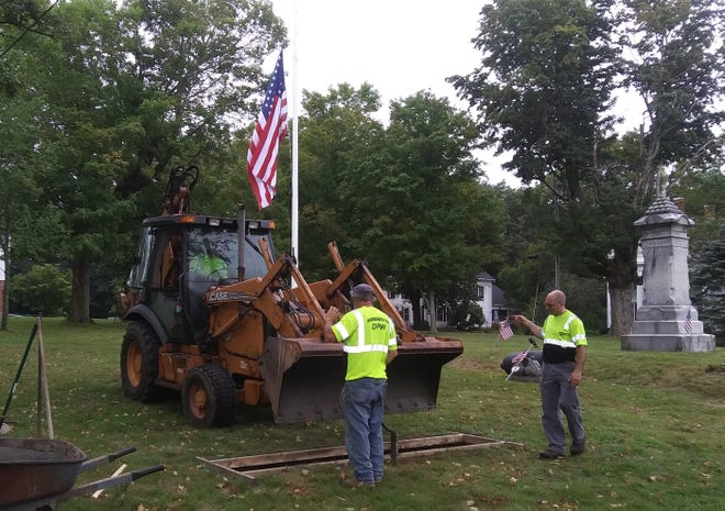 Employees of the Hubbardston Highway Department prepare the foundation for a Vietnam War memorial on the town common on Aug. 30.