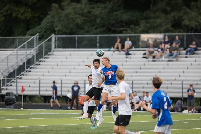 Enka's Jonathan Jimenez-Hernandez and West Henderson's Woody Greene (9) battle for the ball during a match earlier this season at West. West will host county-rival North Henderson on Wednesday.