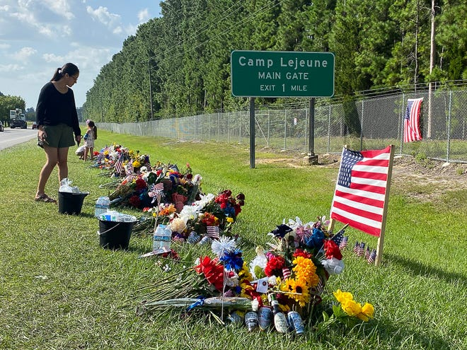 People pay their respects at a roadside memorial along Highway 24 near Camp Lejeune in Jacksonville dedicated to the 11 Marines, one Navy corpsman and one soldier who were killed as the result of an enemy attack while supporting non-combatant evacuation operations in Kabul, Afghanistan.