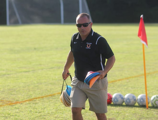 Southwest assistant soccer coach Chip Runyon lays down cones on the field as the Stallions warm up before a recent match against Dixon.