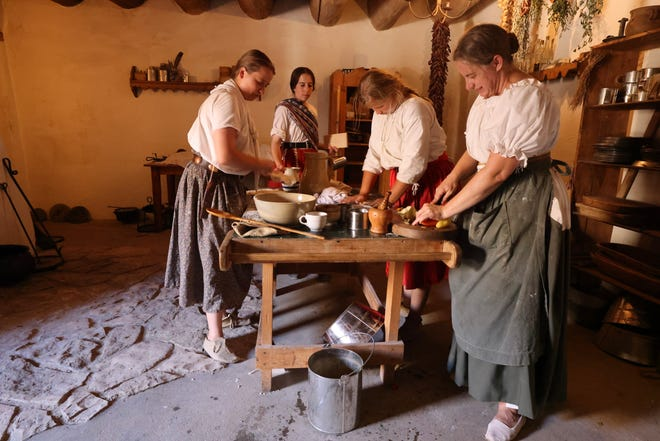 """Living Historians prepare a meal at Bent's Old Fort National Historic Site. The Fort will be featured in an episode of """"A Taste of History,"""" a PBS series hosted by Walter Staib. This photo was taken prior to the current mask mandate at the fort."""