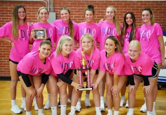 The Midlothian High School volleyball team shows off its trophy from the Arlington High School tournament on Saturday.