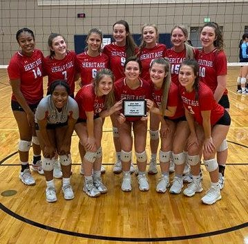 The Heritage High School volleyball team shows off their plaque for winning their bracket at the Volleypalooza tournament in Leander on Saturday.