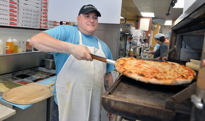 Pete Ferrari pulls out a hot pizza at The Corner Market in Holliston, Aug. 31, 2021.