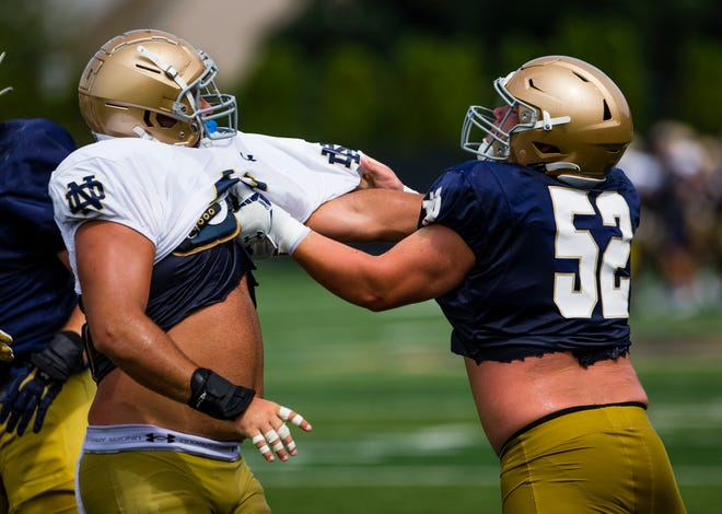 Kurt Hinsh, left, and Zeke Correll square off during Notre Dame football practice, Thursday, Aug. 12, 2021, at the LaBar Practice Complex.