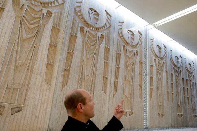 The Rev. Joe Arledge talks about the monolithic concrete angels inside the atrium/courtyard area at St. Patrick Catholic Church in Oklahoma City.