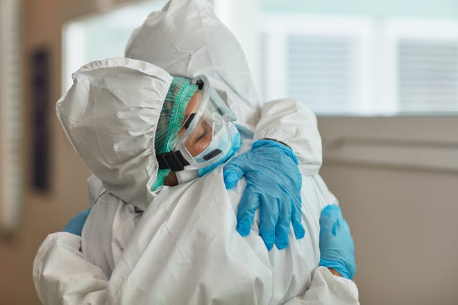 Medical coworkers wearing protective suits, eyewear, and gloves hugging in support and recognition of hard work during COVID-19 pandemic.