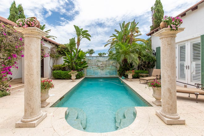 A mural with a lion's head fountain provides a focal point at the far end of the pool area at 2258 Ibis Isle Road E. The house is listed at $4.1 million.