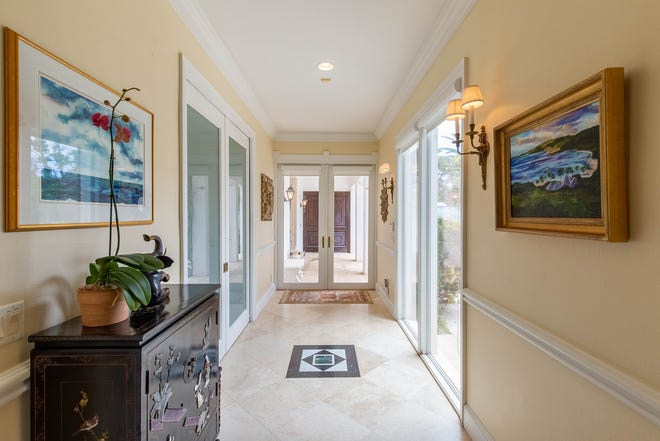 Viewed from the foyer, thebreezeway bordering the courtyard can be seen through the glass front doors.
