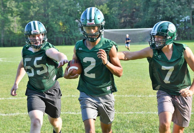Dover quarterback Darian Lopez-Sullivan, center, is pursued by teammates Josh Stanley, left, and Hunter Linton during Division I football practice last week at Bellamy Field.