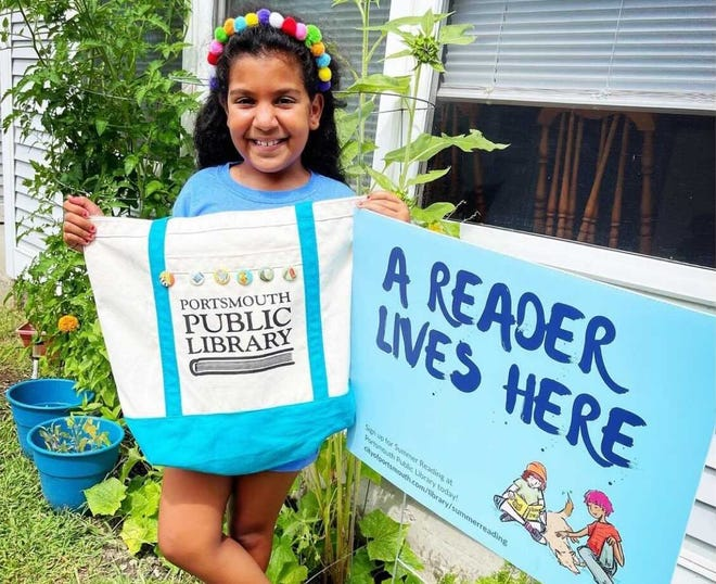 Little Harbour second-grader Lulu proudly displays her Portsmouth Public Library bag and lawn sign, along with other prizes from this year's Summer Reading Program.