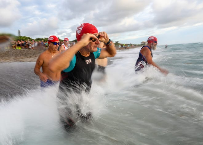 Athletes race into the Atlantic Ocean at the start of the Loggerhead Triathlon at Carlin Park in Jupiter, FL, Saturday, August 28, 2021. The race course consisted of a 3/8 mile ocean swim, 13 mile bike and flat 3.1 mile run.